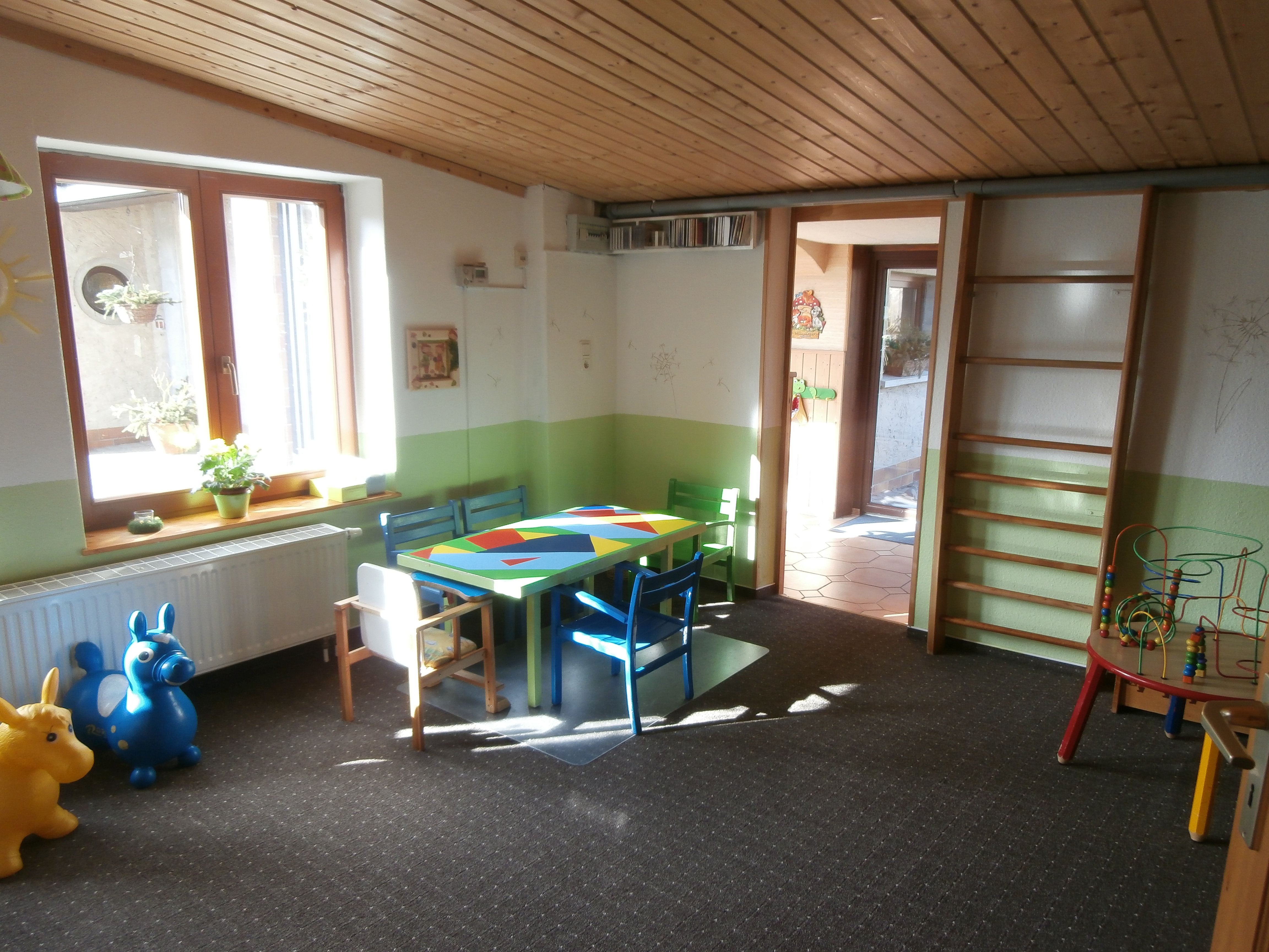 Farben: hellgrün, dunkelblau, Holzdecke, grauer Teppichboden