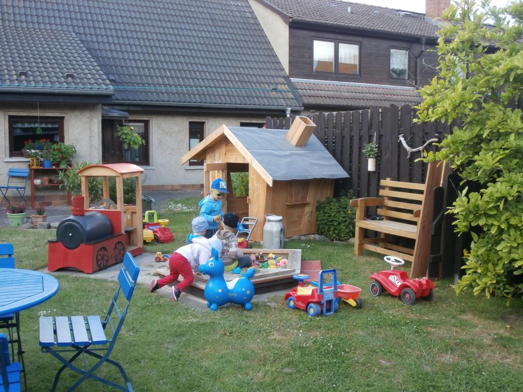Blick in den Garten mit Spielgeräten und Häuschen.