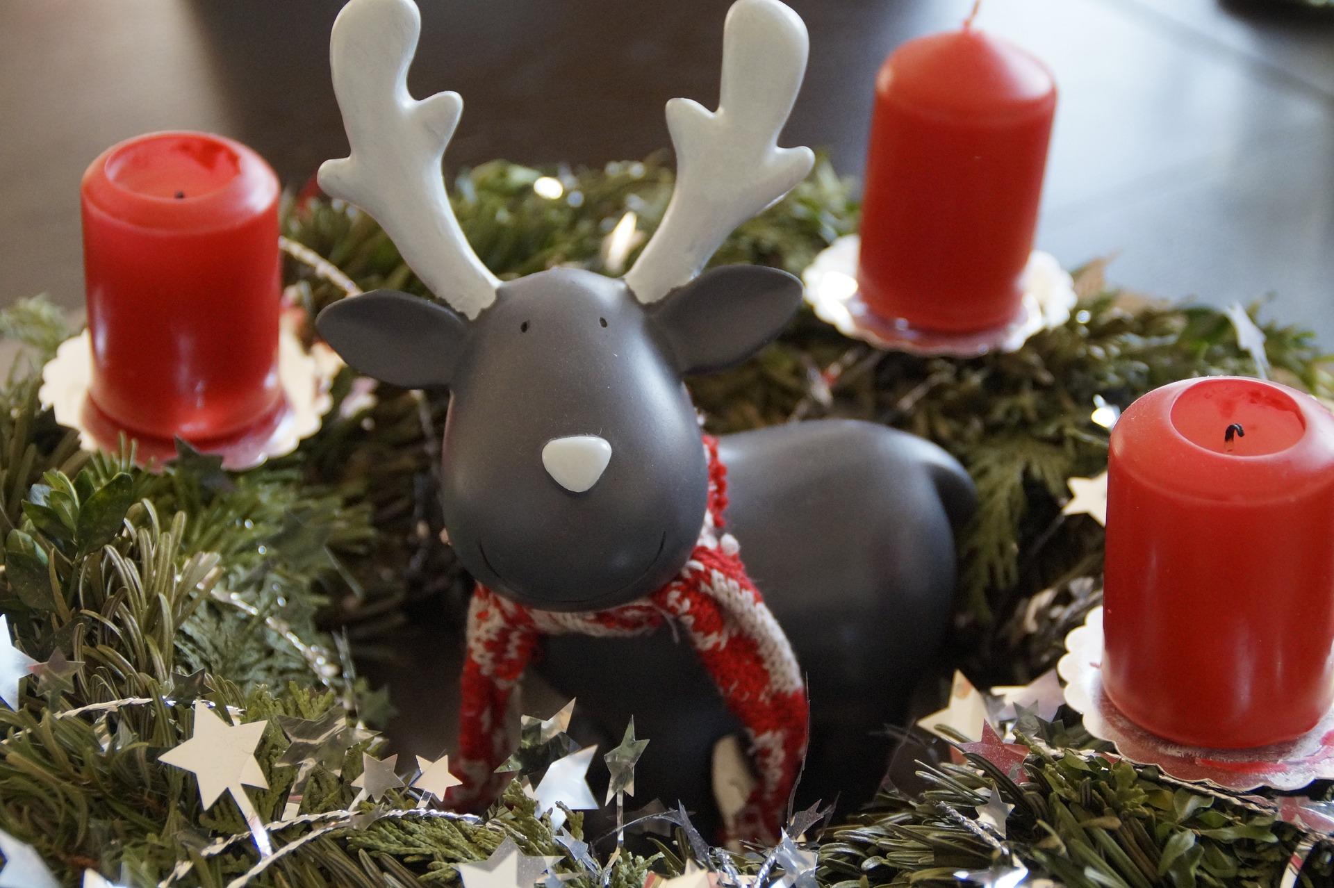 Adventskranz mit roten Kerzen und einer Elchfigur in der Mitte.